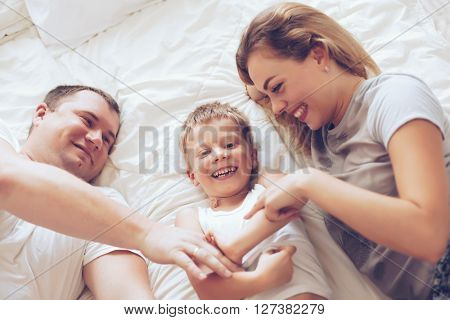 Young parents with their 6 years old little son dressed in pajamas are relaxing and playing in the bed at the weekend together, lazy morning, top view.