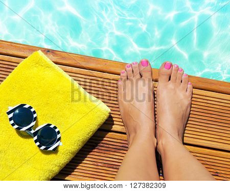 Summer holiday fashion selfie concept - woman on a wooden pier at the pool with summer accessories; sunglasses, towel