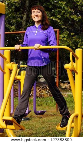 Brunette woman exercising lower body and legs on outdoor gym concept of healthy and sporty lifestyle