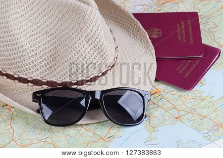 German travel passports and sunglasses with straw hat and map