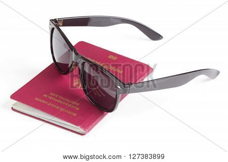 German travel passport and sunglasses over white
