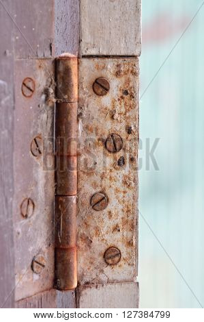 old and rusty door hinge on wooden frame