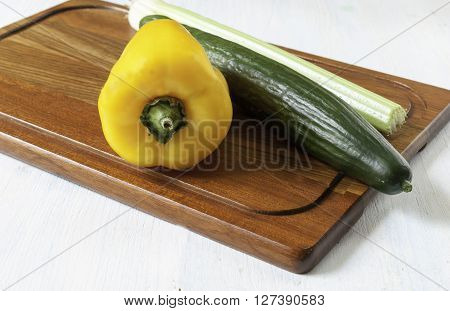 yellow pepper with a knife lying on a kitchen cutting Board