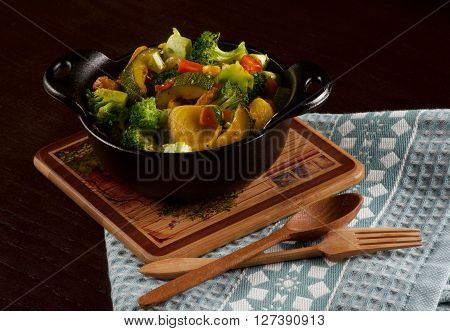 Delicious Homemade Colorful Vegetables Ragout with Zucchini Carrots Broccoli Leek and Red Bell Pepper in Black Iron Stewpot with Wooden Spoon and Fork closeup on Blue Napkin