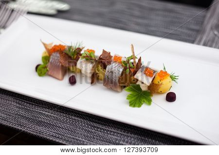 Salted and marinated herring on creamy cheese, beer and black bread chips, potatoes and red caviar