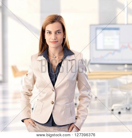 Confident caucasian blonde young businesswoman standing at bright office, smiling, looking at camera, hands in pocket, woman suit, copyspace.