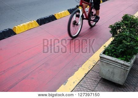 cyclist on a red bike path in modern city