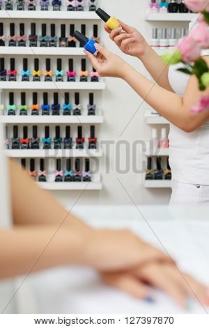 Manicurist choosing between two colors of nail polish