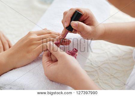 Hands of master applying beautiful marsala nail polish