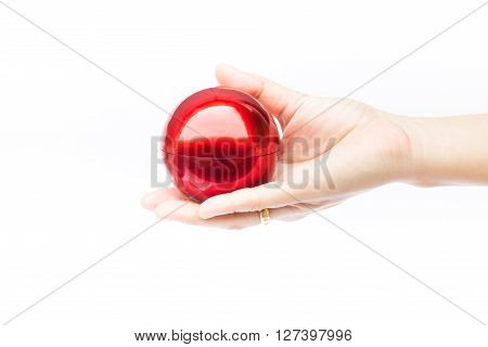 Hand on shiny red ball on white background stock photo