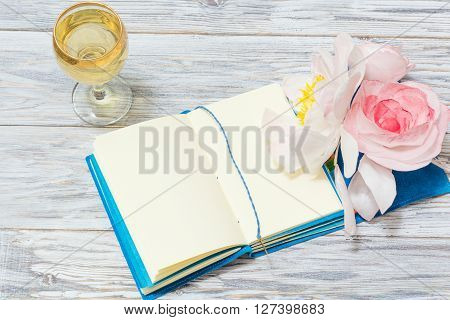 notepad white wine and flowers flat lay
