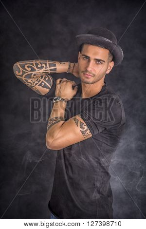 Handsome and stylish young man with black bowler hat and t-shirt. Cool tattoos on arms