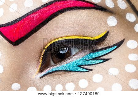 Photo of young woman with professional comic pop art make-up. Creative beauty style. Photos shot in studio. Close up