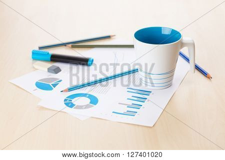 Office workplace with coffee cup and charts on wooden desk table