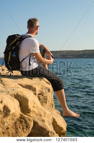 Hiker with bare feet sits on a rocky sea shore resting after a walk and looks into the distance