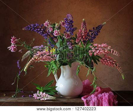 Still life with a bouquet of pink and purple lupine in the white jug.