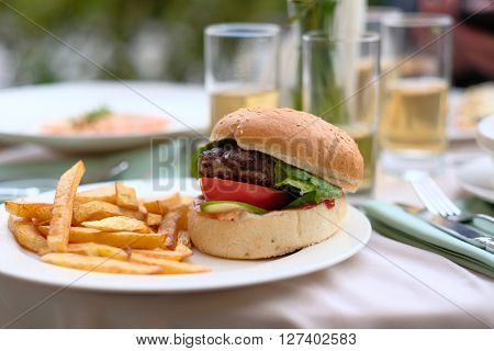 Hamburger and fries at restaurant outdoor table