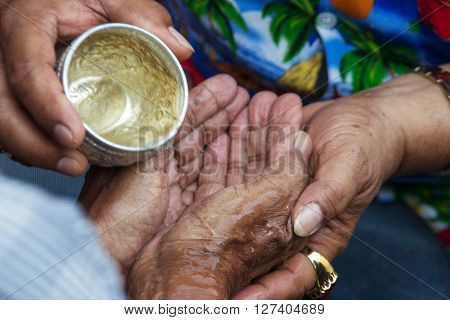 Close Up Hand Watering Old Family For Respect In Songran Ceremony