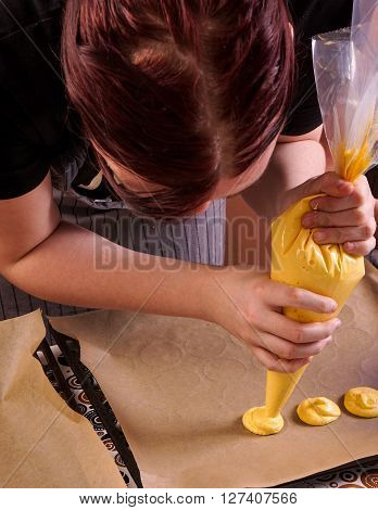 Piping tray of macaroons. Woman makes macaroon