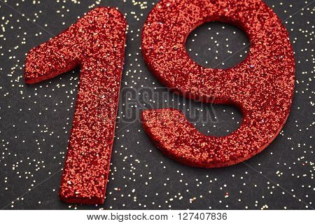 Number nineteen red color over a black background. Anniversary. Horizontal