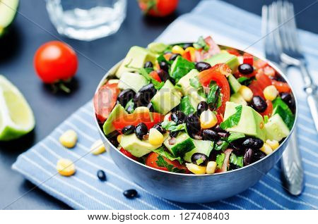 Black beans corn avocado cucumber tomato salad with lime dressing.