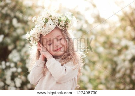 Smiling baby girl 3-4 year old posing in meadow over flowers. Wearing floral wreath outdoors. Childhood.
