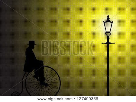 A silhouette of a gentleman on a penny farthing in the light of a street lamp