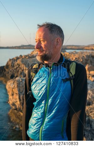 Bearded man on sea coast. Traveler on the sea coast rests and looks at the sun