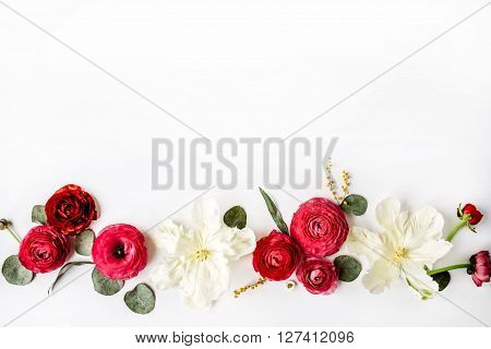 Pink and red roses or ranunculus white tulips and green leaves on white background. Flat lay top view
