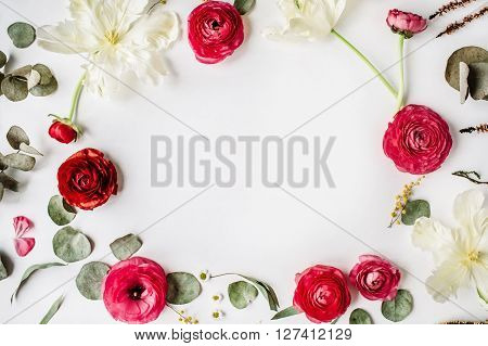 wreath frame with pink and red roses or ranunculus white tulips and green leaves on white background. Flat lay top view