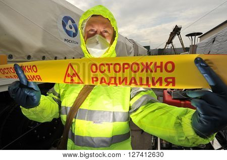 Saint-Petersburg Russia April 6 2016: A man in a protective suit holding a ribbon with the inscription in Russian