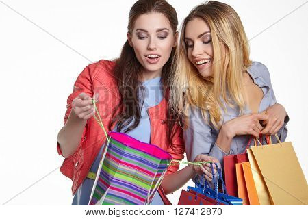 shopping, sale and gifts concept - two smiling teenage girls with shopping bags