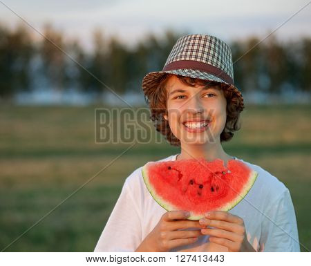 teenager eating watermelon on a haystack