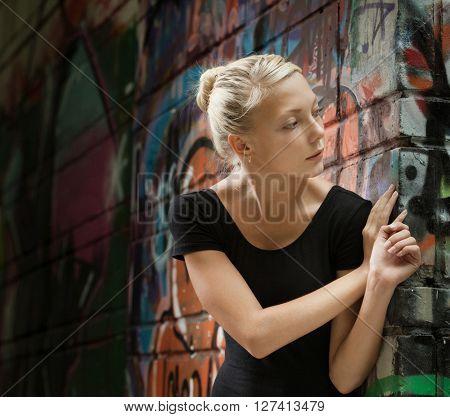 beautiful girl on a city street near a wall of graffiti