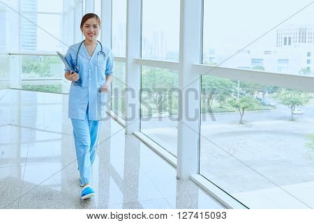 Smiling Vietnamese medical worker walking in hospital