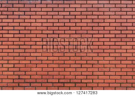 Background of lightly weathered dark red brick wall with dark grouting