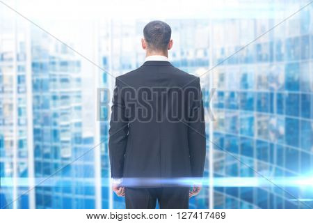 Backview of businessman, blue background