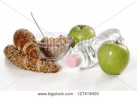 healthy breakfast with muesli, green apple and wholegrain croissant