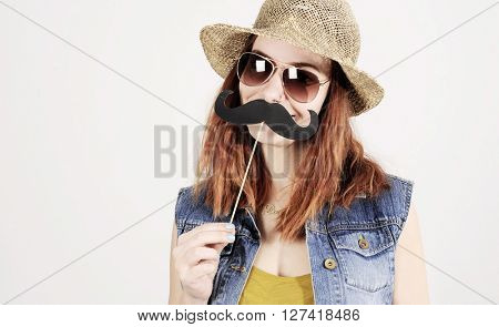 funny trendy fashion girl with paper mustache playing with emotion