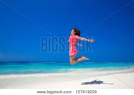 Enjoyment. Happy Free Woman Jumping Over Sea And Blue Sky, Brunette Smiling Girl In Red Dress On Tro
