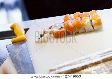 Sushi Rolls With Salmon Lay On Cutting Board