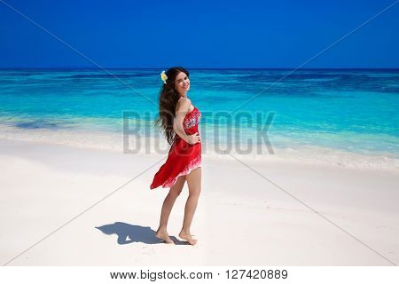Beautiful Smiling Woman In Red Dress Enjoying On Exotic Sea, Tropical Beach. Summer Outdoor Portrait