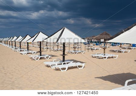 Different parasols and sun loungers on the beach on Tavira island before heavy stormAlgarve. Portugal