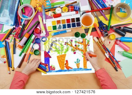 child drawing rabbit with carrot on kitchengarden near house, top view hands with pencil painting picture on paper, artwork workplace