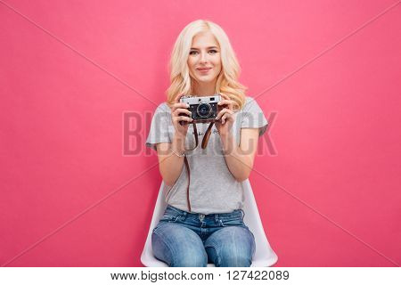 Pretty woman holding photo camera over pink background