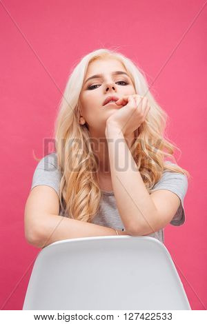 Beautiful blonde woman sitting on the chair over pink background and looking at camera