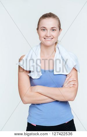 Smiling woman with towel standing with arms folded isolated on a white background