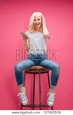 Cheerful blonde woman sitting on the chair and listening music over pink background