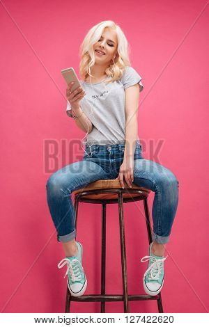 Smiling attractive woman sitting on the chair with smartphone and headphones over pink background