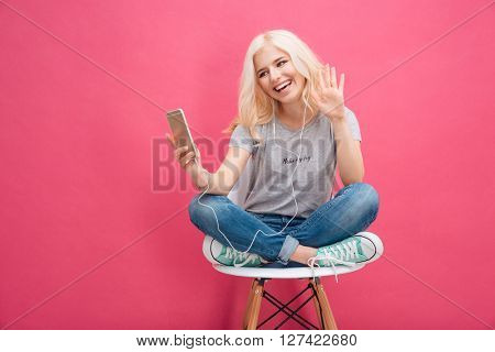 Smiling woman video chatting on smartphone over pink background